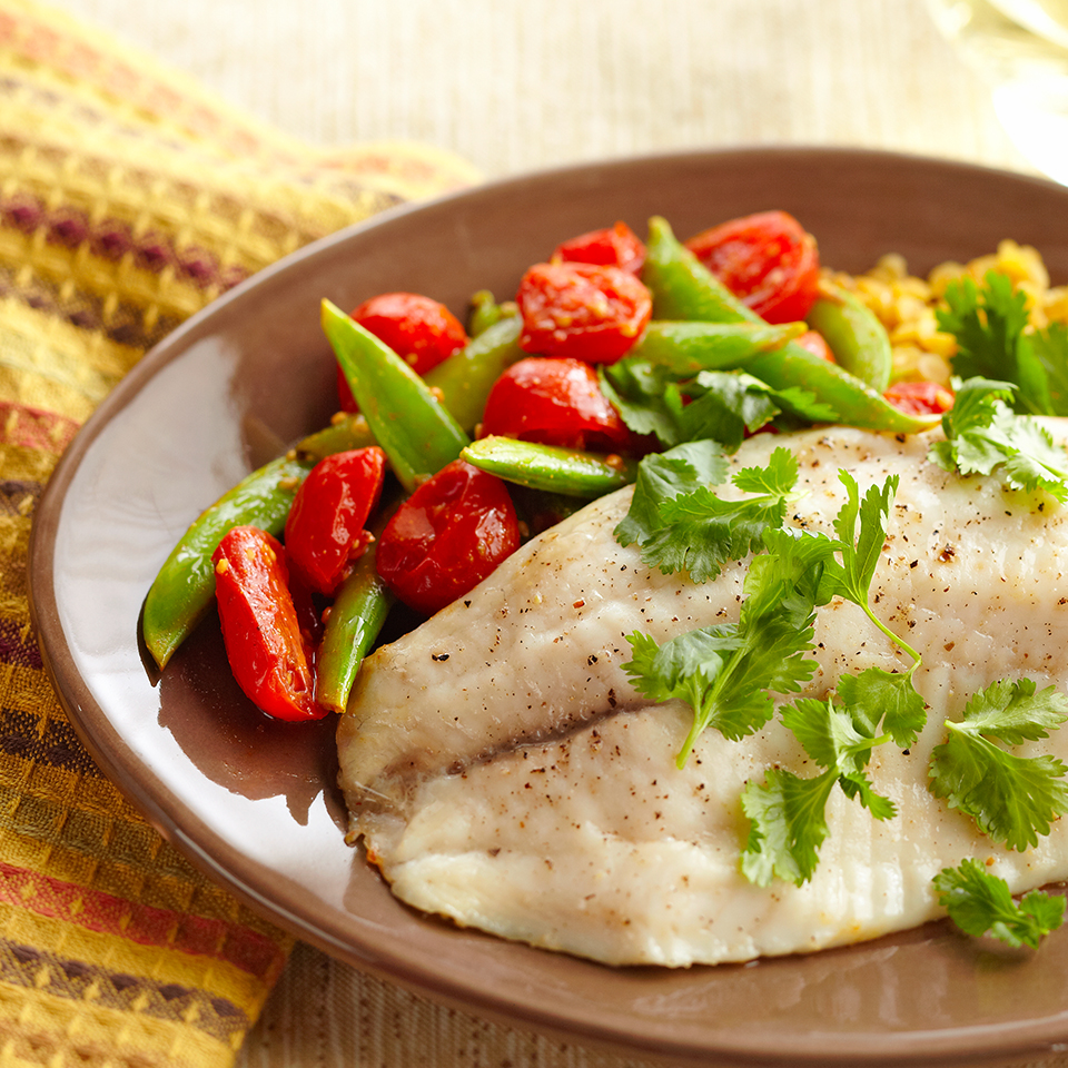 Baked tilapia fillets are served alongside curry-flavored lentils, pea pods, and cherry tomatoes in this colorful and healthy 25-minute dinner recipe. With a few substitutions you can turn this dish into a sandwich or a bowl (see recipe variations, below).