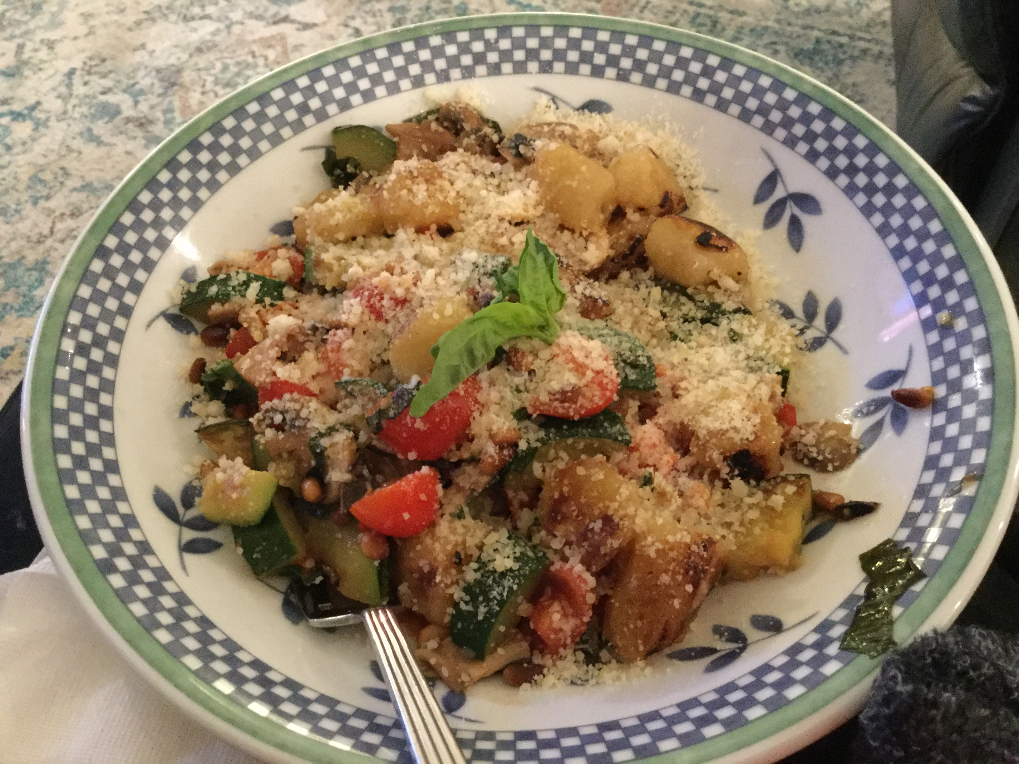 "Little pillows of potato pasta are cooked with mushrooms, grape tomatoes, zucchini, and fresh basil, and served topped with Parmesan cheese crisps. ""Potato gnocchi with wonderful crisp vegetables and basil make a delicious, rustic meal,"" says Dawn Camacho."