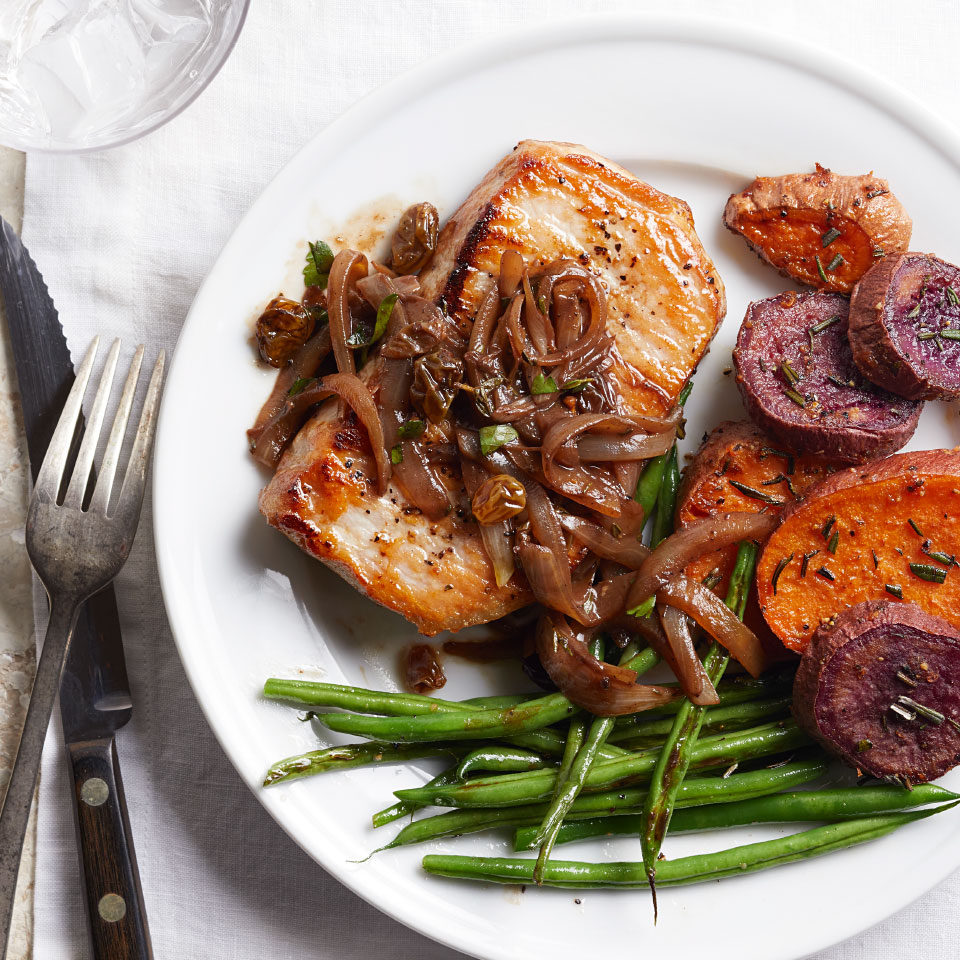Balsamic onions and raisins add a burst of sweet and savory flavor to pan-seared pork chops. Round out this healthy dinner recipe with sweet potatoes and green beans.