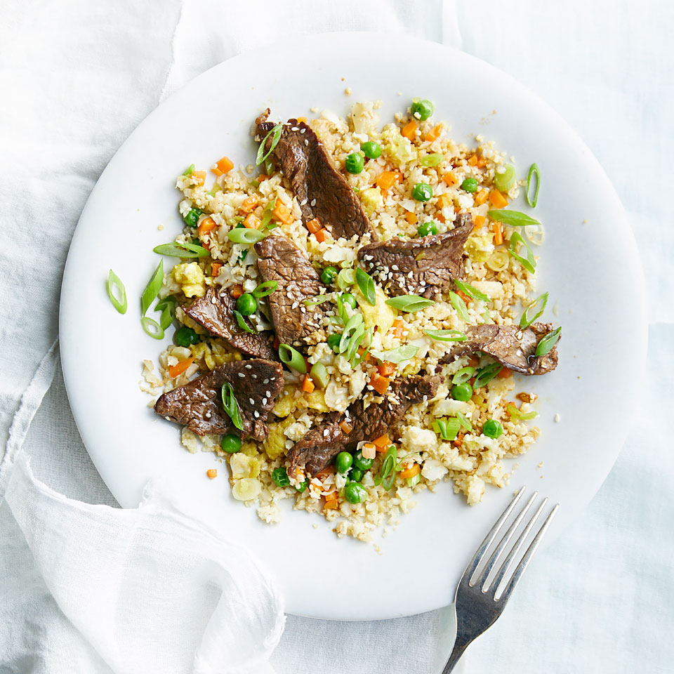 "You could argue that fried rice is really all about the ""add-ins,"" so why not skip the grain itself and save some calories with cauliflower while you're at it? If you want to make this recipe vegetarian, swap sliced mushrooms for the steak. Either way, you don't have to be on a low-carb diet to love this 30-minute dinner. Source: EatingWell Magazine, April 2019"