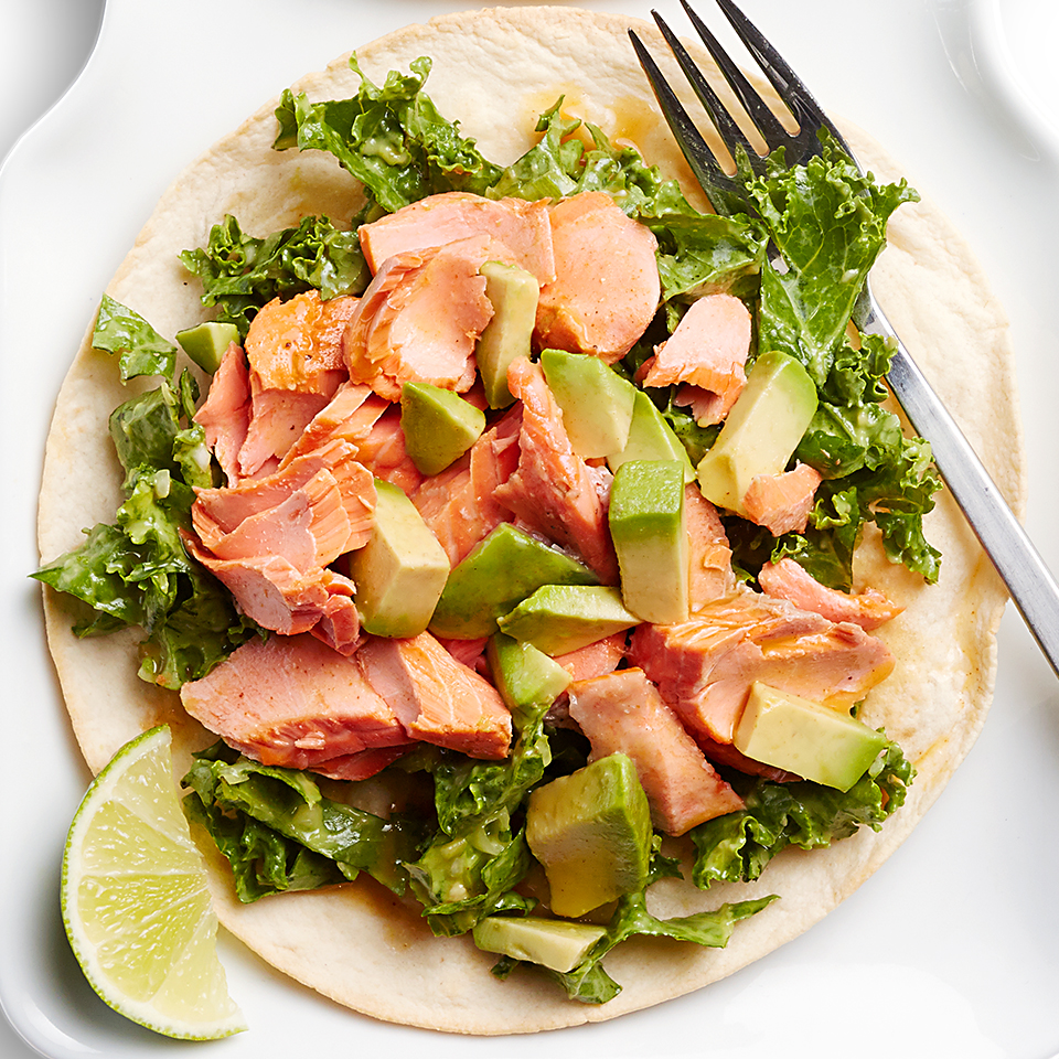 Citrus-chili marinated wild salmon takes center stage in this tostada recipe that's bursting with citrus-dressed kale and chunks of creamy avocado.