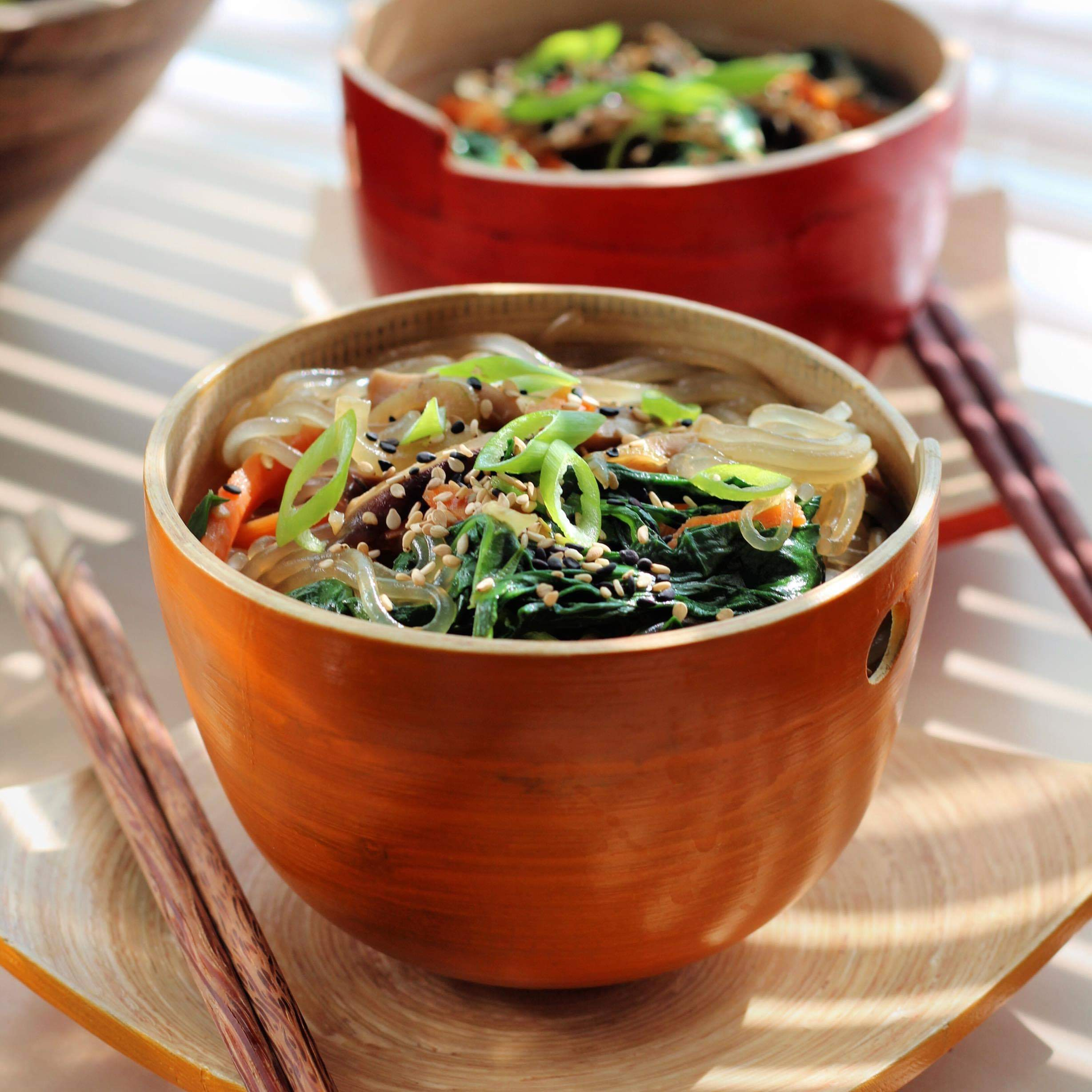The Korean noodles used in this dish are made from sweet potato starch. They turn translucent when cooked, which is why we call them glass noodles. In this recipe, they are tossed with carrots, mushrooms, spinach and a sweet sesame-soy dressing for a gluten free and vegan meal.