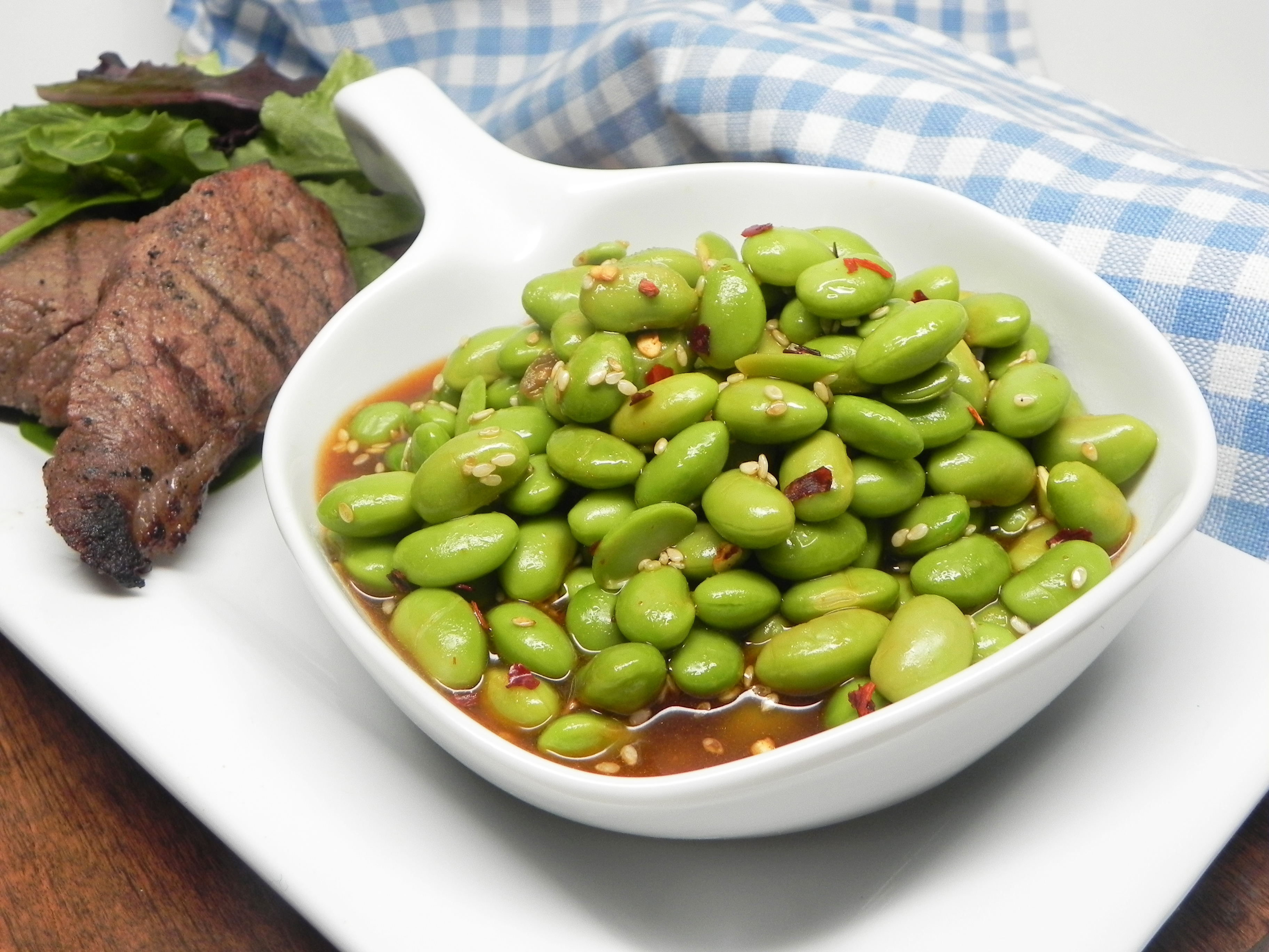 """Cook edamame over high heat with sesame oil, vinegar, oyster sauce, sriracha sauce, and sesame seeds, finishing with a sprinkle of red pepper flakes. """"A unique twist to traditional edamame,"""" says BandC. """"We had this at a restaurant and found oyster sauce is the key to this dish!"""""""