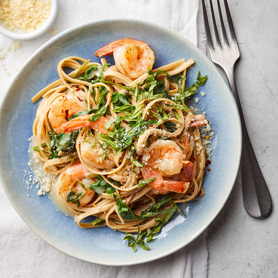 Yogurt makes a fine substitute for cream in the sauce for this easy pasta recipe. Just warm the yogurt (do not boil) and add some pasta-cooking water to thin it out. Lemon and fresh basil brighten up the whole-wheat pasta and complement the shrimp in this quick dinner recipe.