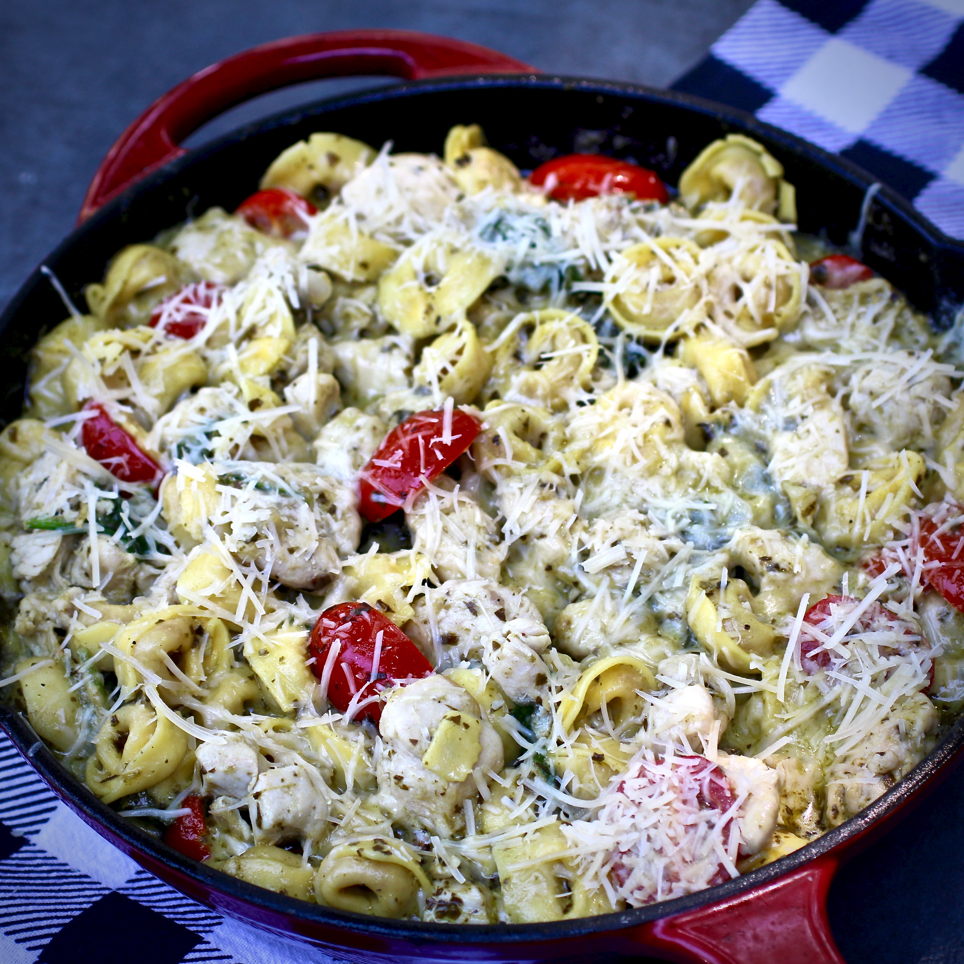 """You'll start by browning cubes of chicken in a skillet with a little olive oil. You'll deglaze the pan with broth, scraping up any browned bits, and then add prepared pesto, a little cream, Parmesan cheese, spinach, tomatoes, and cheese tortellini for the last 5 to 10 minutes. """"A delicious chicken and tortellini pesto dinner that needs only one pan to create,"""" says My Hot Southern Mess."""