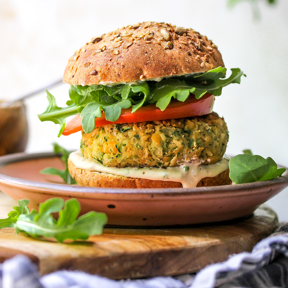 This vegan burger recipe is one you'll want to make again and again. Savory chickpea and zucchini patties are topped with a creamy, herb-flecked tahini ranch sauce, juicy tomato slices and peppery arugula for a satisfying and healthy homemade veggie burger. Serve them on buns or stuff them in pitas.