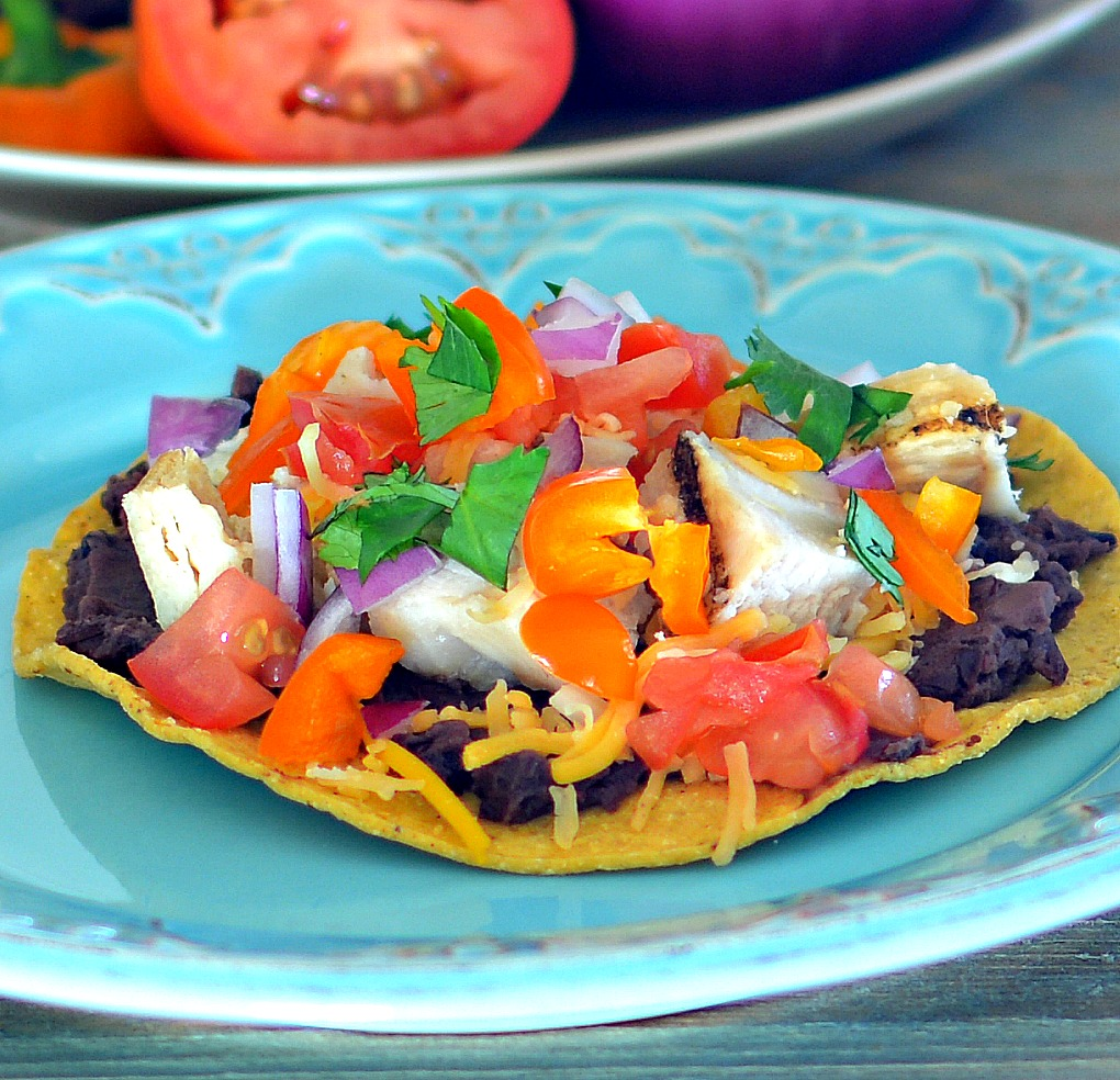 """These simple seasoned chicken, refried beans, and veggie tostadas are baked in the oven until crispy. Finish them with salsa, sour cream, and a sprinkle of cilantro. """"Excellent flavors!"""" raves bd.weld. """"Didn't have green peppers so I used orange and use refried black beans."""""""