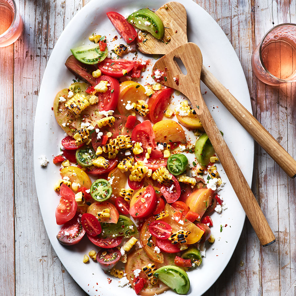 The roasted pepper and corn salsa that tops this gorgeous tomato salad has a kick from the tart sherry vinegar and moderately spicy and fruity Aleppo pepper. Red-wine vinegar and ground ancho chile are good alternatives. Grill some chicken, fish or other protein along with the corn for an easy summer dinner. Source: EatingWell Magazine, July/August 2019