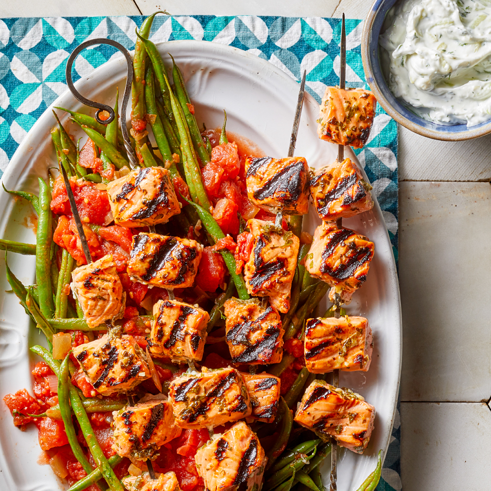 This easy grilled salmon recipe is sure to help you win your next backyard BBQ. Lemon, garlic and herbs make a simple, flavorful marinade for the healthy fish souvlaki (souvlakia is the Greek word for kebabs), and the yogurt-based tzatziki sauce is one of the traditional pleasures of Mediterranean cuisine. A side of Greek-style green beans completes this healthy dinner recipe that's as suited to entertaining as it is to family meals. Source: Diabetic Living Magazine, Fall 2019