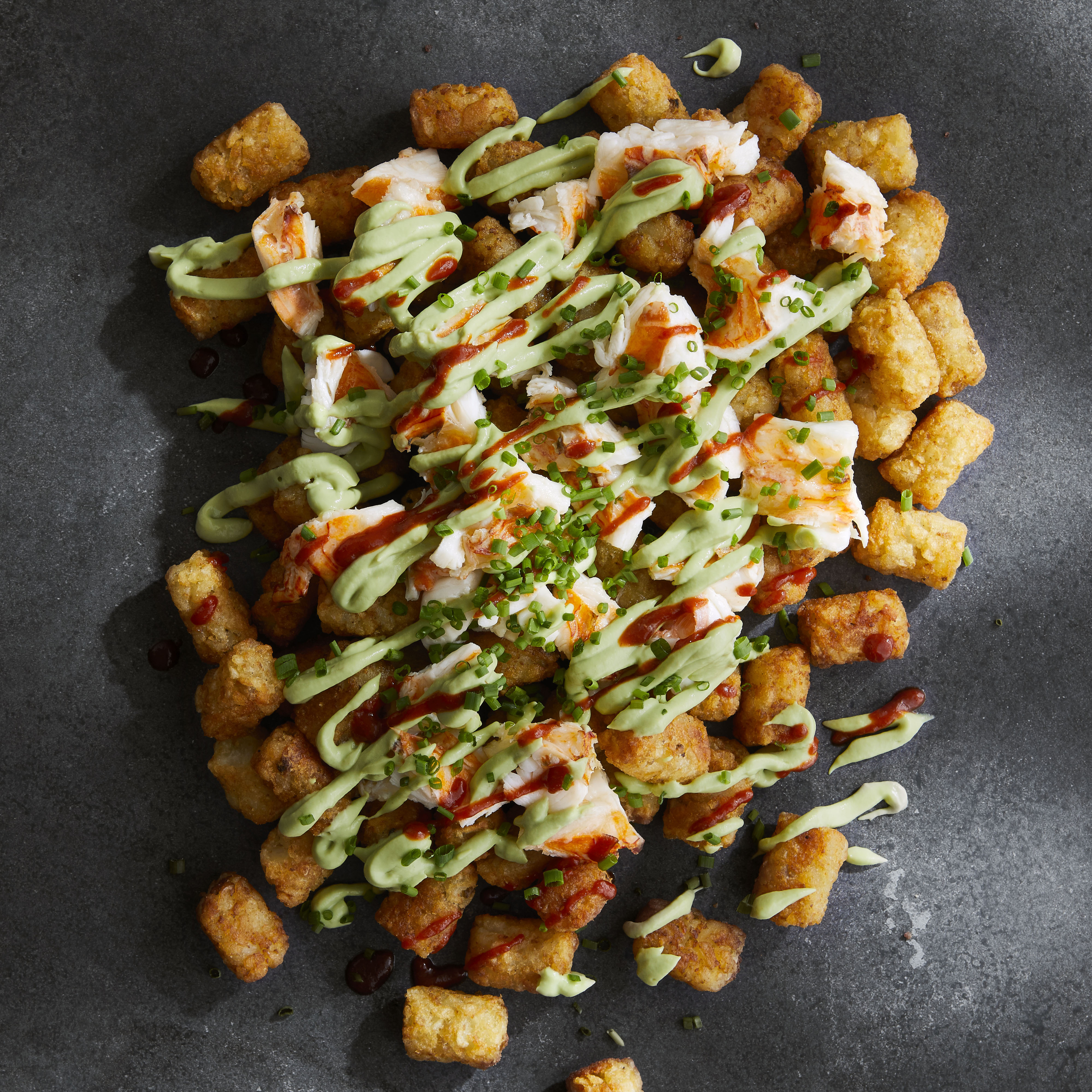 "Dan Whalen, the recipe submitter, says: ""I'm from New England, where lobster is a tradition. My favorite way to use it: Combine a fancy ingredient like lobster with a humble ingredient like a tot. The avocado crema and hot sauce really make this dish, though."""