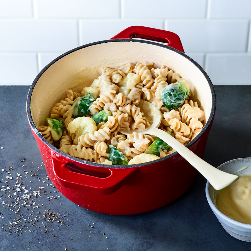 Taking a minute to sizzle some garlic in olive oil is a simple way to pep up the cheese sauce for this easy homemade mac and cheese, and the flavor plays well with the cauliflower and Brussels sprouts in this family-friendly pasta dish. This recipe is designed for you to make a big batch of the cheese sauce to use in different dishes: Stir it into pasta and veggies to make this pasta a one-pot dinner then use it for Cheesy Beef Enchilada Casserole later in the week (see Associated Recipes). Or simply serve it over your favorite steamed vegetables for an easy side dish. If you'd rather make just enough sauce for this pasta, simply cut the sauce amounts in half. Source: EatingWell Magazine, September 2019