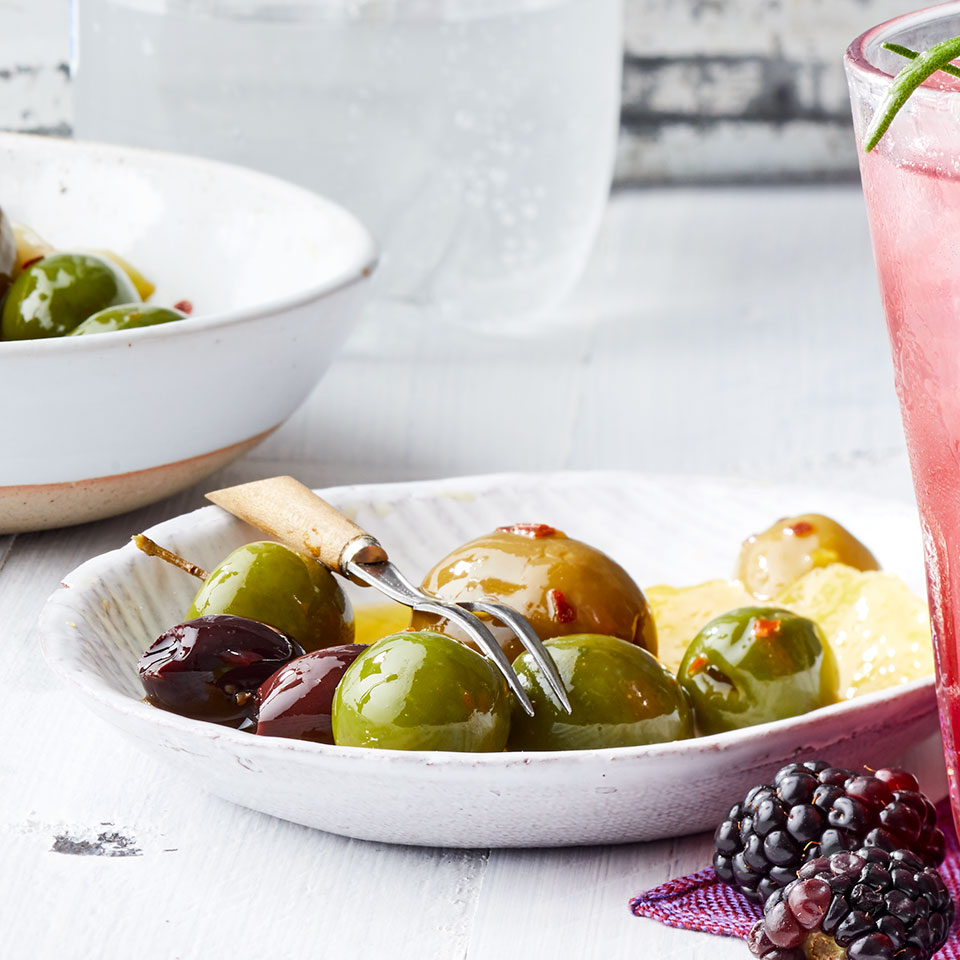 Simply pour warm aromatic oil over a selection of olives to infuse them with loads of flavor fast. These olives are a wonderful easy party appetizer--add any leftovers to salads or simply snack on them.