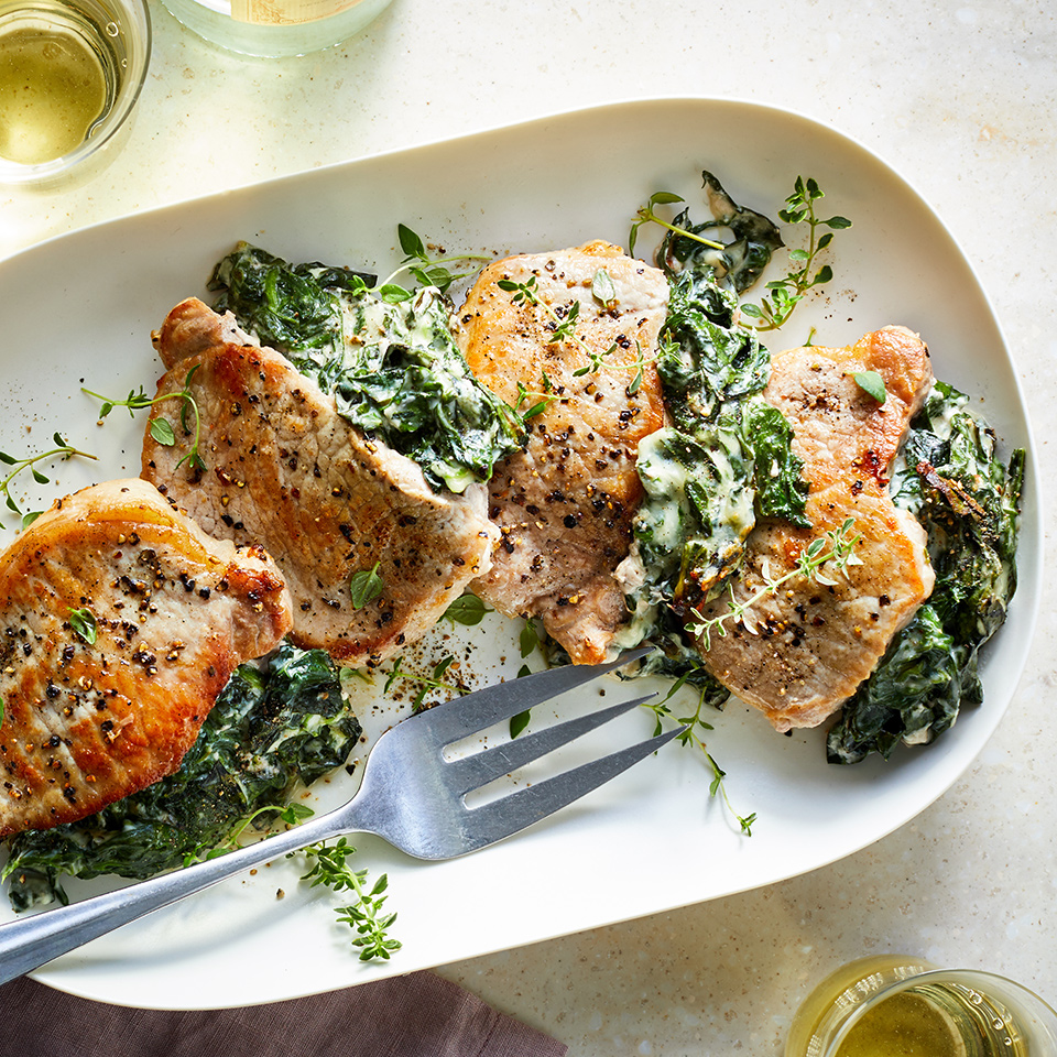 With a flavor reminiscent of creamed spinach stuffed inside a tender, seasoned pork chop, this dinner is sure to please. To really make this recipe work best, look for center-cut pork chops with a thin rim of fat on the outside edge. Alternatively, if you'd rather not stuff the pork chop, you can just simply serve the cheesy spinach-and-kale mixture alongside the pork.