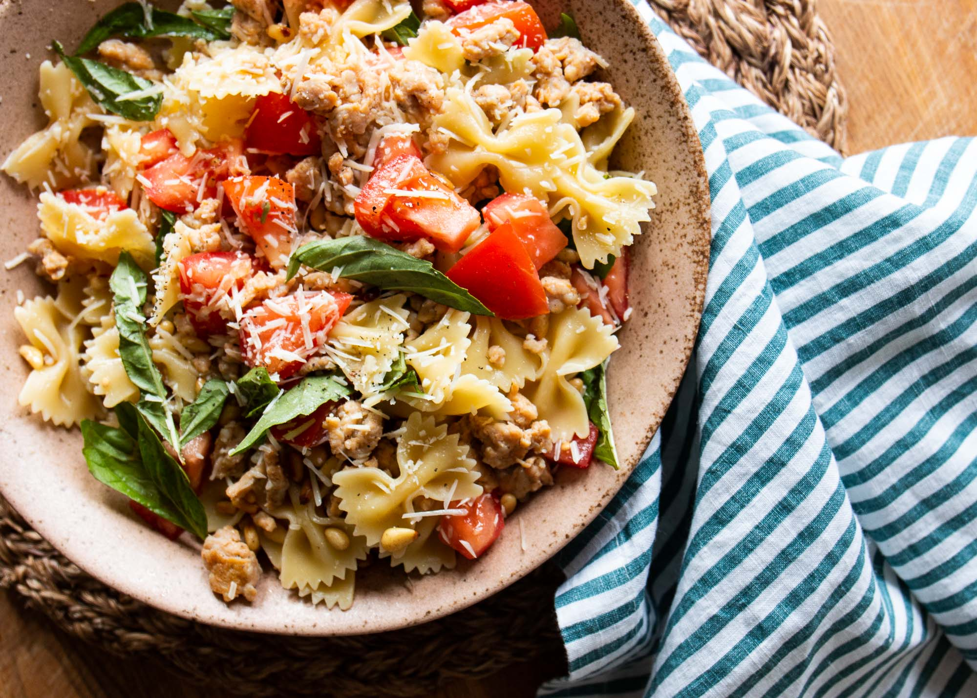 Toasted pine nuts combine with crumbled chorizo sausage, fresh basil, chopped tomatoes, and Parmesan cheese. Toss this savory mixture with hot farfalle pasta, and dress it up with oil and vinegar.