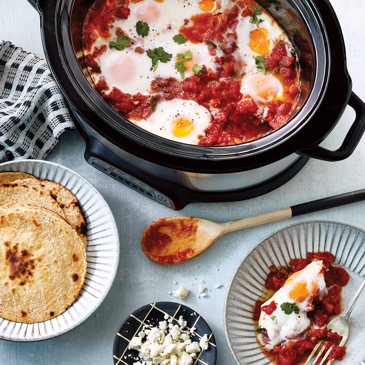 Start your day with hearty, slightly spicy shakshuka full of Southwestern flavor. To avoid one large egg blob on top, be sure to make wells in the sauce using a spoon. It's important to use corn tortillas and not flour tortillas if you're going gluten free. Lightly toast the tortillas, if desired. Source: Everyday Slow Cooker