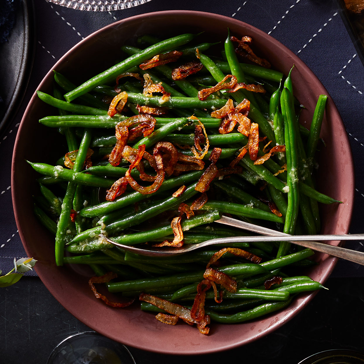 Here's a new way to delight your green-bean-loving guests. The genius of this easy green bean recipe is in the dressing, which is made with savory oil that has also been used to fry shallots and garlic.
