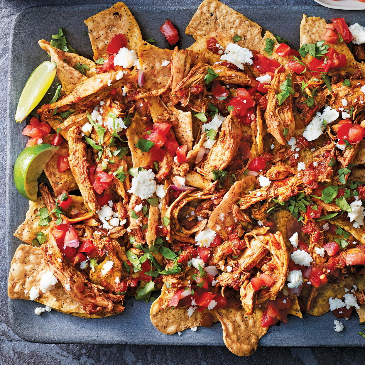 Host a cocktail party or game night and serve guests these tasty slow-cooker turkey nachos. The turkey picks up smoky flavor from the chili powder and cumin, and the chips and toppings give the dish varied textures. Serve with margaritas or cold beer and fresh lime wedges, if desired.