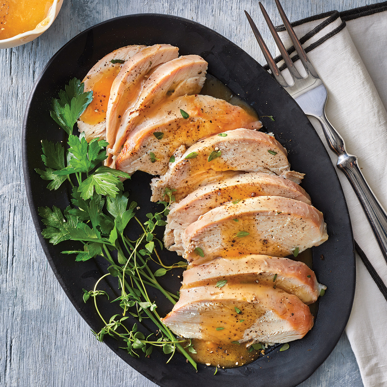 Depart from the expected roasted whole turkey for Thanksgiving dinner, and serve this succulent, slow-cooker turkey breast instead. You'll delight guests with a new dish and also save yourself hands-on time and effort. As a bonus on Turkey Day, this recipe leaves your oven free for stuffing and casseroles. If whole turkey breast isn't available, ask your butcher to cut up a whole turkey and give you the whole turkey breast. To make this recipe gluten free, use gluten-free Dijon. For a pretty presentation, serve with fresh thyme and cilantro sprigs.