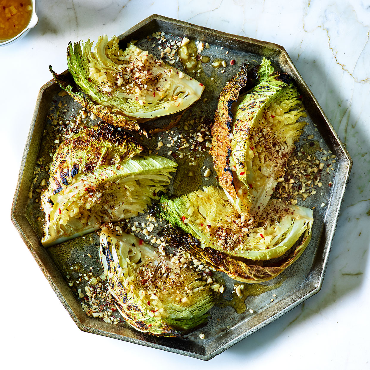 Easy Savoy cabbage recipes can be far and few between, especially ones that are as delicious as this whole roasted cabbage. The outer cabbage leaves blacken during the long cooking time, but when removed they reveal a meltingly tender center. Orange blossom water adds delicate aroma to the vinaigrette that's drizzled on top. Serve alongside roast beef or pork, or over mashed potatoes as a main course.