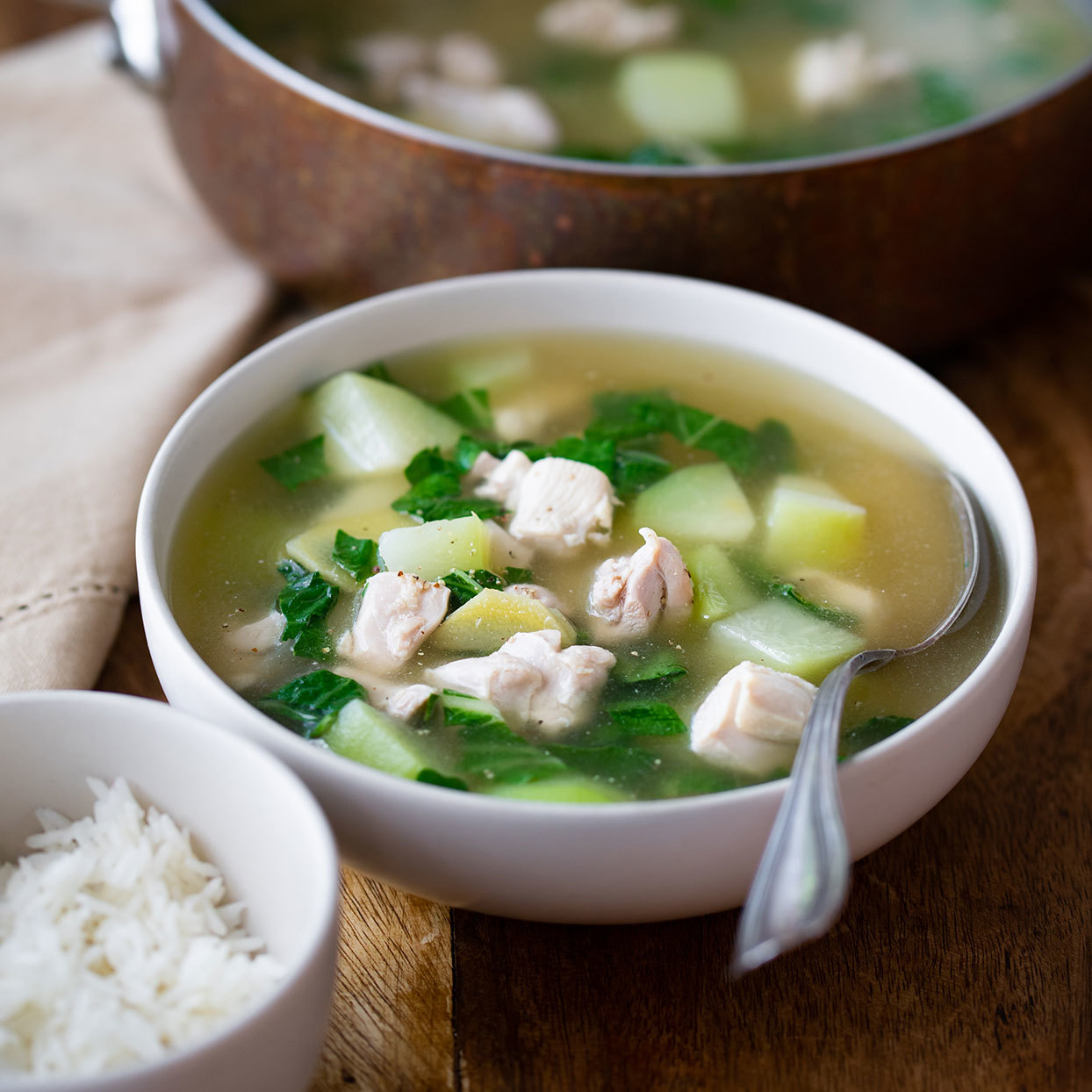 Tinola, a comforting chicken soup seasoned with plenty of ginger and garlic, has countless variations throughout the Philippines. The soup calls for malunggay leaves (aka moringa), which can be found fresh or frozen at Asian markets. Bok choy is a good substitute. Feel free to increase the amounts of garlic and fish sauce for an even more flavorful soup. Serve this easy and healthy chicken soup on its own or with jasmine rice, quinoa or wild rice.