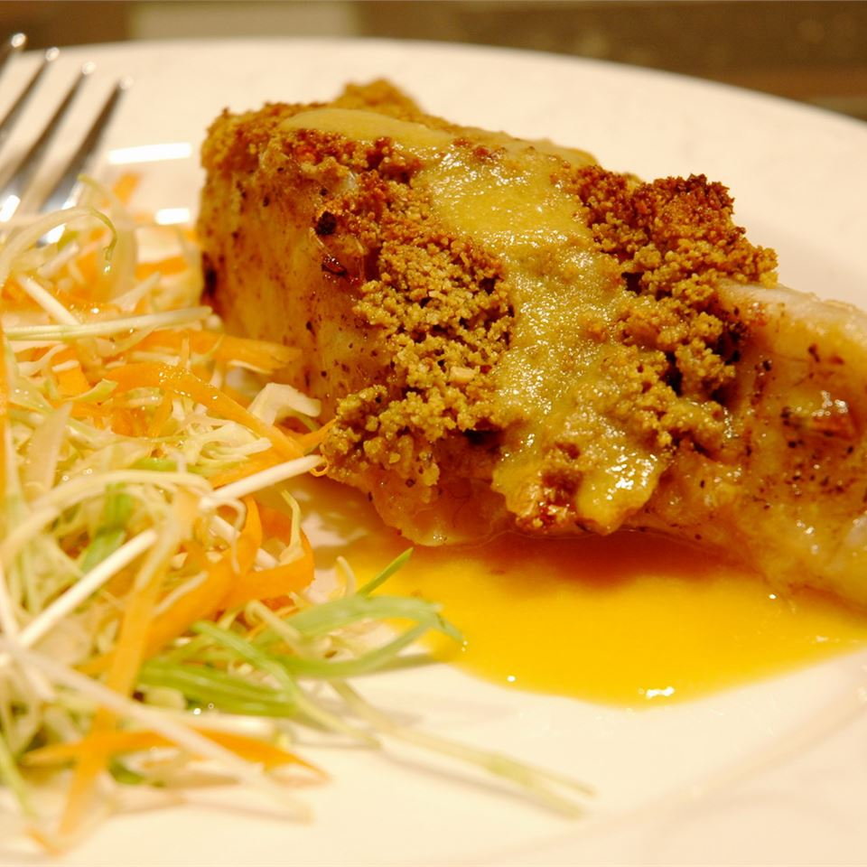"Bring the island vacation to your kitchen with this impressive recipe. Seared sea bass fillets are topped with a macadamia nut crust and a velvety fresh mango sauce. ""This is the best fish recipe I have ever prepared,"" says recipe reviewer luvs2entertain."