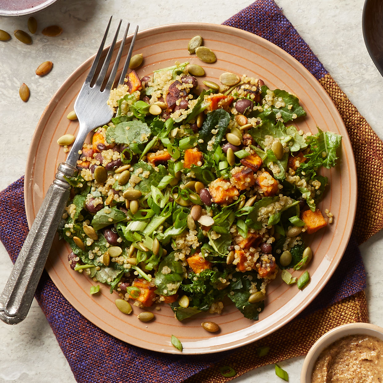 Precooked quinoa helps keep this healthy salad recipe quick and simple. Loaded with black beans, kale, and avocado, this recipe is as filling as it is nutritious. You can also make the sweet potatoes and dressing ahead.