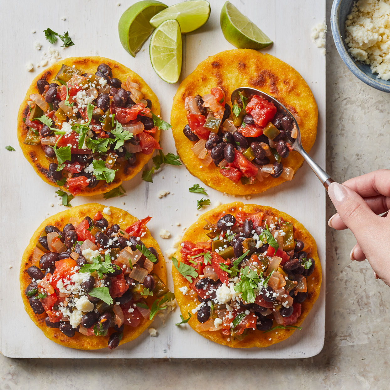 These corncakes are a common style of flatbread in Colombia and Venezuela. Arepas are made with precooked cornmeal and served warmed with butter or cheese, or split open and filled, or topped, as we've done here. Our arepas filling is loaded with fragrant spices and vegetables to elevate the dish. Source: EatingWell Magazine, December 2019