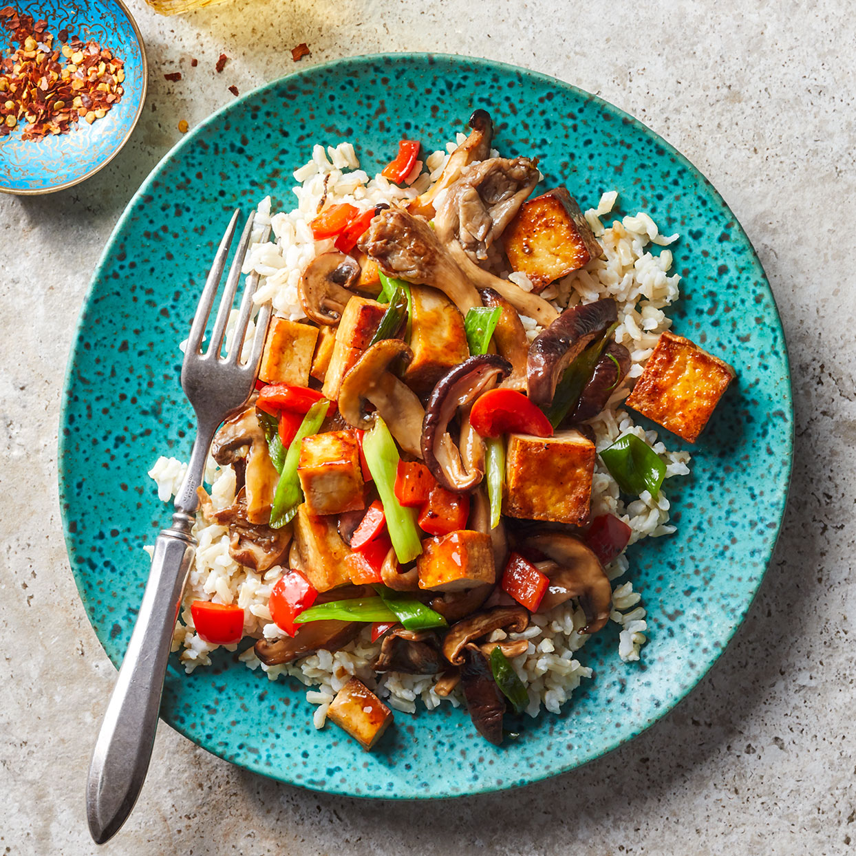 This tofu veggie stir-fry is quick and easy, making it a great go-to weeknight meal. Baked tofu has a firm, toothsome texture that crisps well in a hot pan. You can find it in flavors like teriyaki and sesame, both of which are delicious here. Or opt for a smoked version, which has the same texture with a more robust flavor. Serve over brown rice.Source: EatingWell Magazine, December 2019