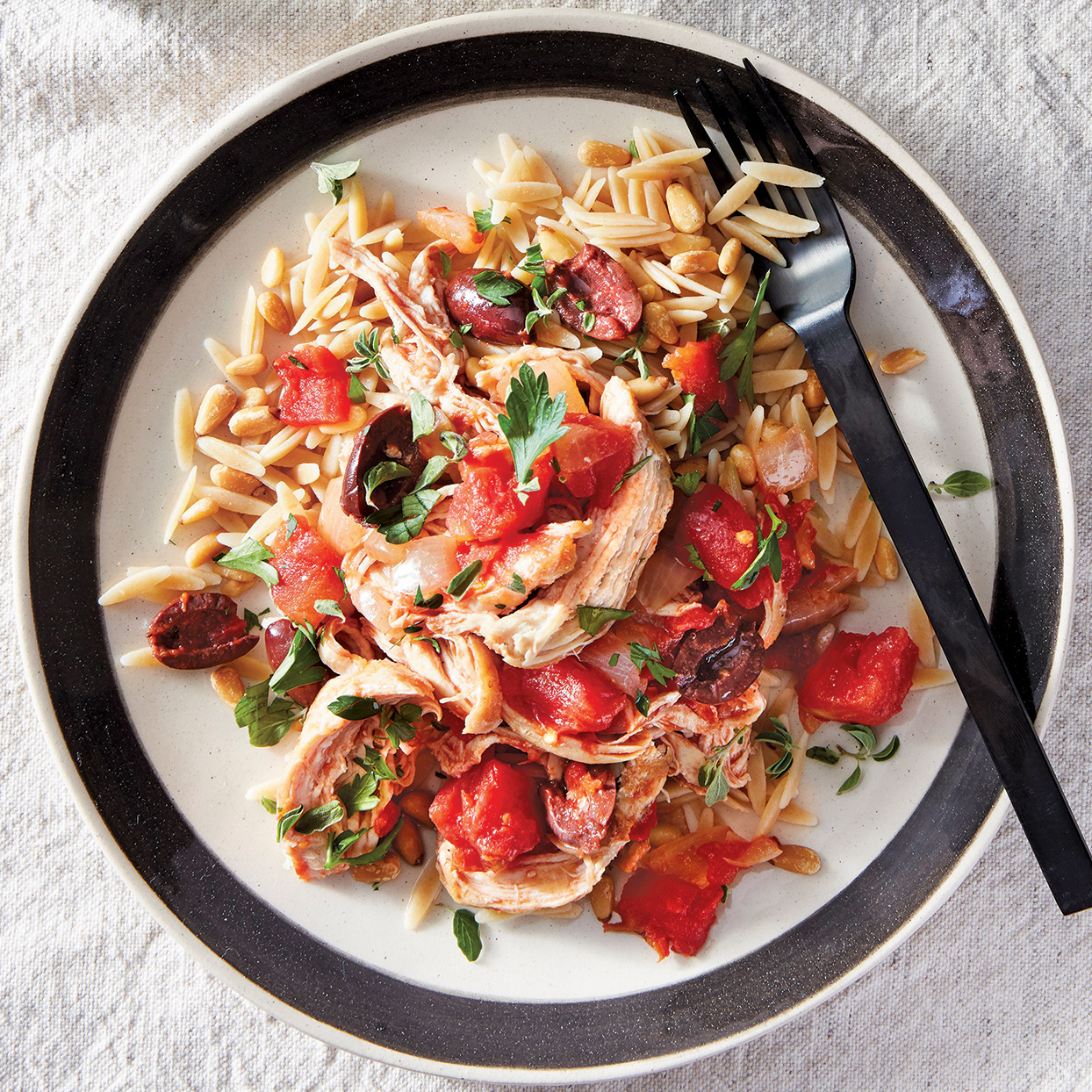 Let your slow cooker do the bulk of the work and end up with a meal that fulfills all your Mediterranean-food cravings. The mix of onions, tomatoes, kalamata olives, oregano and parsley adds pleasing acidity to the browned chicken, while toasted pine nuts lend interest to the orzo.
