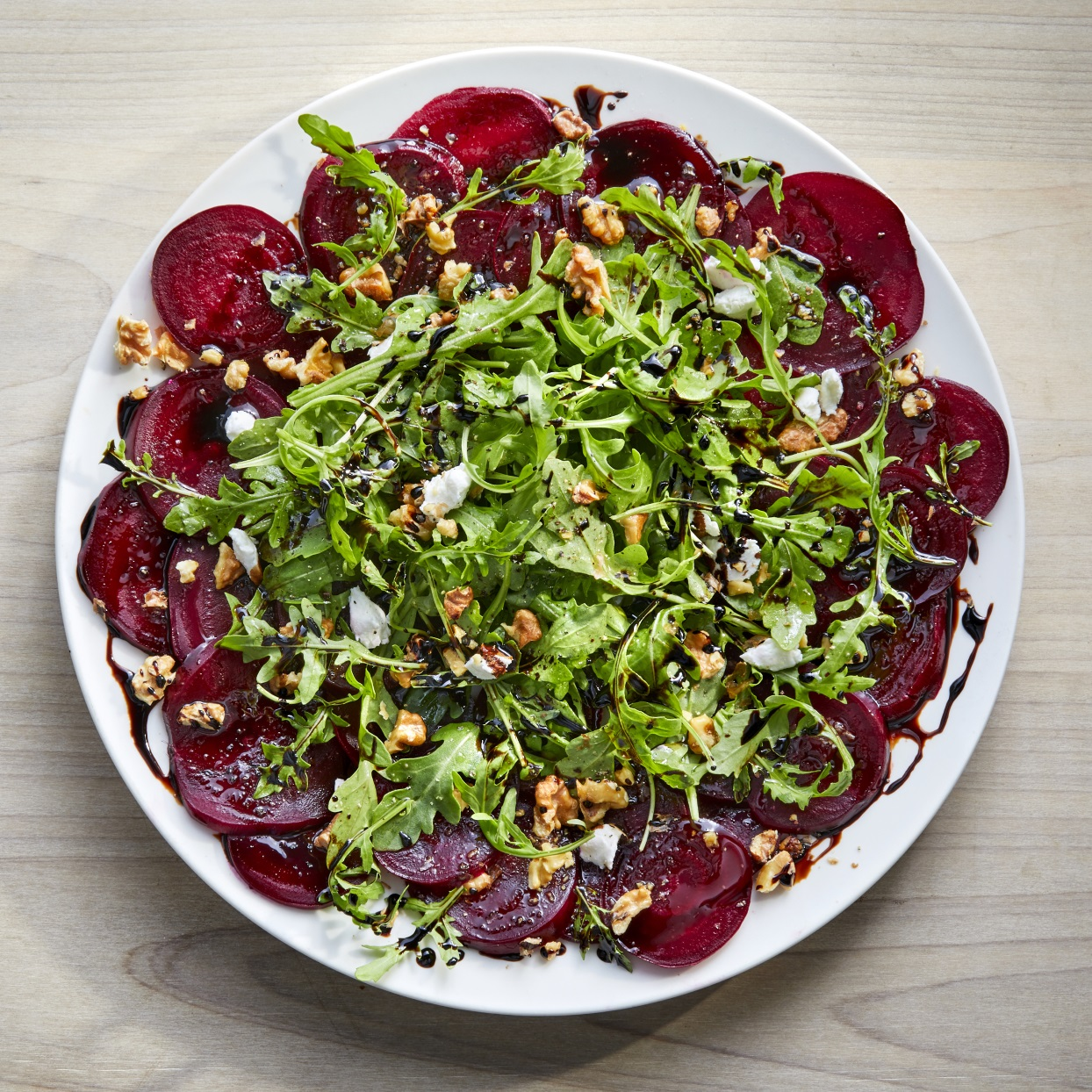 This stunning winter salad gets its sweet, earthy flavor from roasted beets and balsamic vinegar. Creamy goat cheese and peppery arugula add color and balance, while toasted walnuts add crunch. A mandoline is the best way to get thin, even slices from the roasted beets.