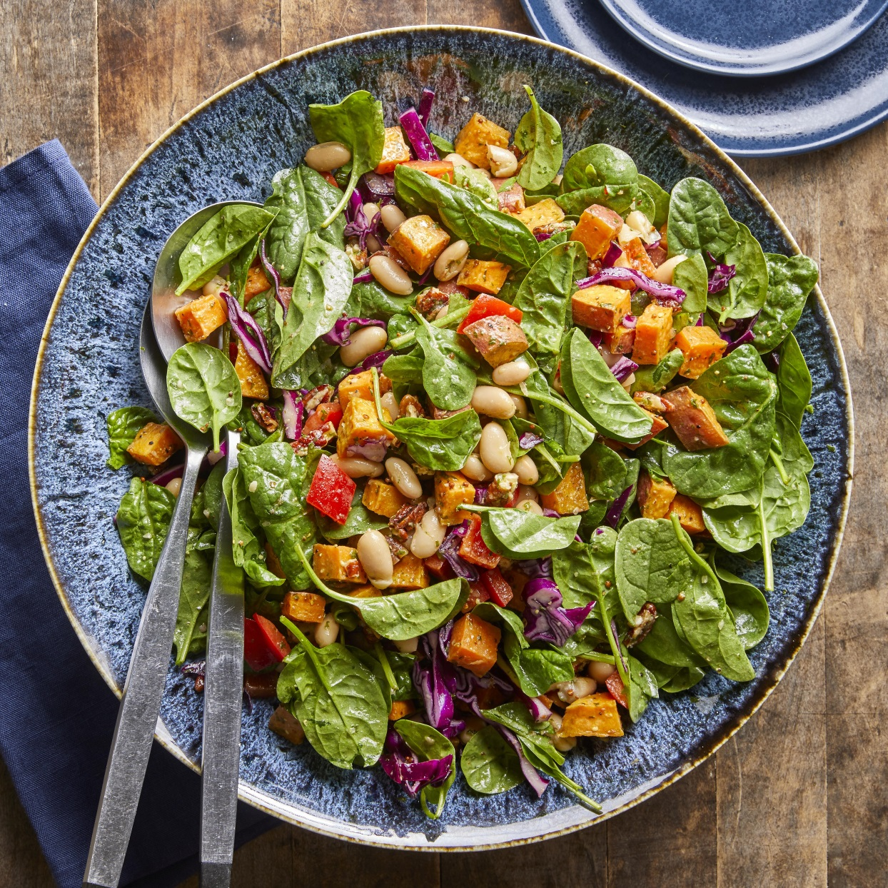 Roasted sweet potatoes are paired with spinach, cabbage and white beans and tossed together with a bright basil dressing in this healthy main dish salad.