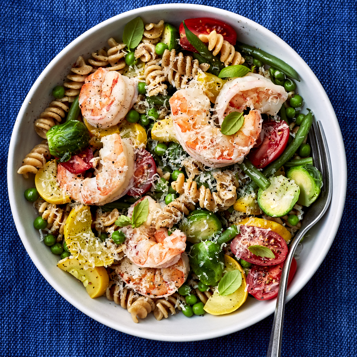 Forget the fuss: this one-pot meal has it all--garlic, shrimp, vegetables and plenty of fresh basil. Cleanup after this healthy dinner is a breeze and it's quick too, done in less than 30 minutes. Once you get comfortable with this weeknight recipe, get creative by substituting zucchini for the summer squash and swapping out the Brussels sprouts for broccoli or cauliflower. Source: EatingWell.com, December 2019