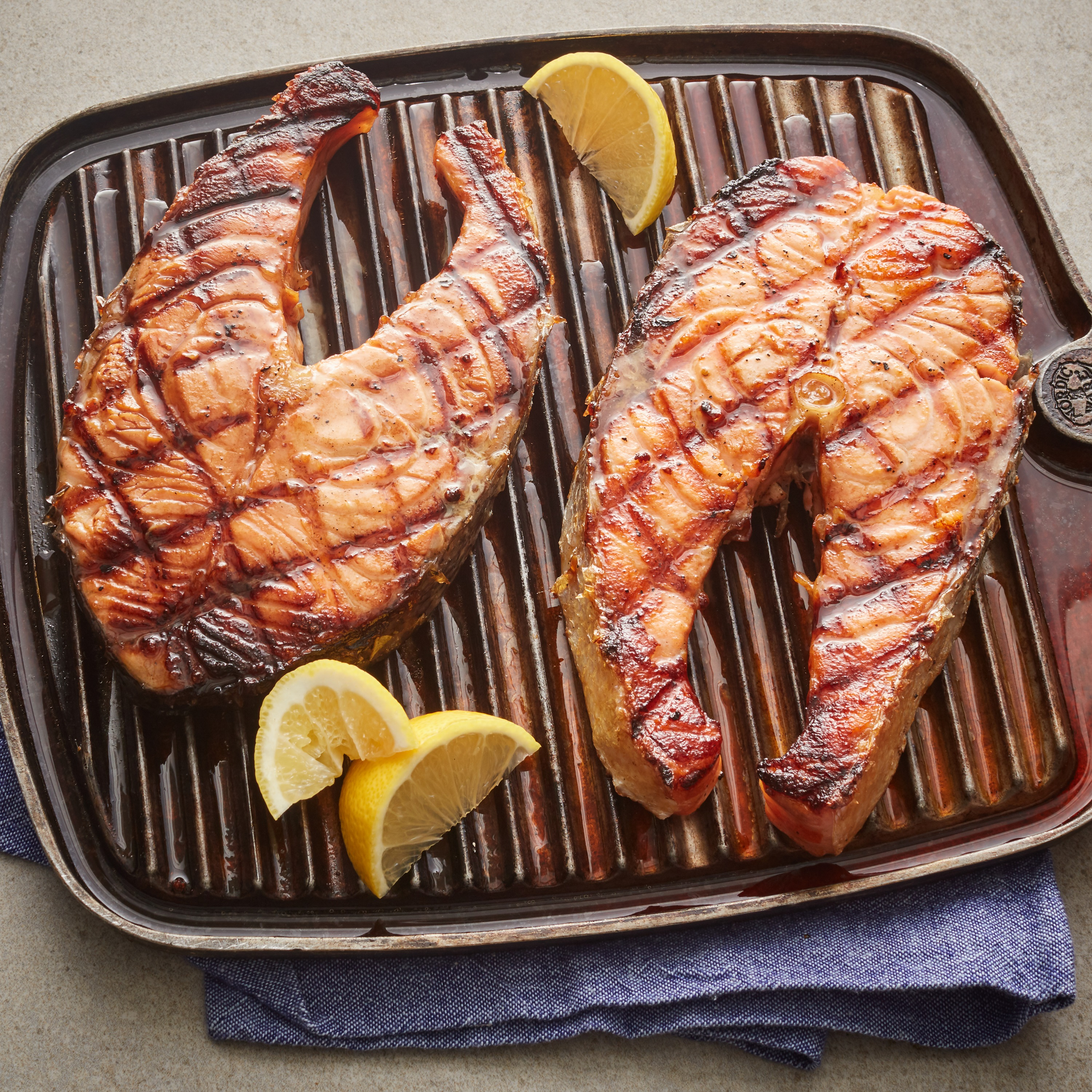 """Here's a very simple salmon recipe that starts with a marinade of soy sauce, red wine, ginger, and black pepper. Grill over hot coals for about 5 minutes per side, basting frequently with extra marinade. """"This seafood treat is best prepared over a charcoal fire, but in bad weather the oven broiler will do,"""" says Alan Harasimowicz. """"The secret is in the marinade."""""""