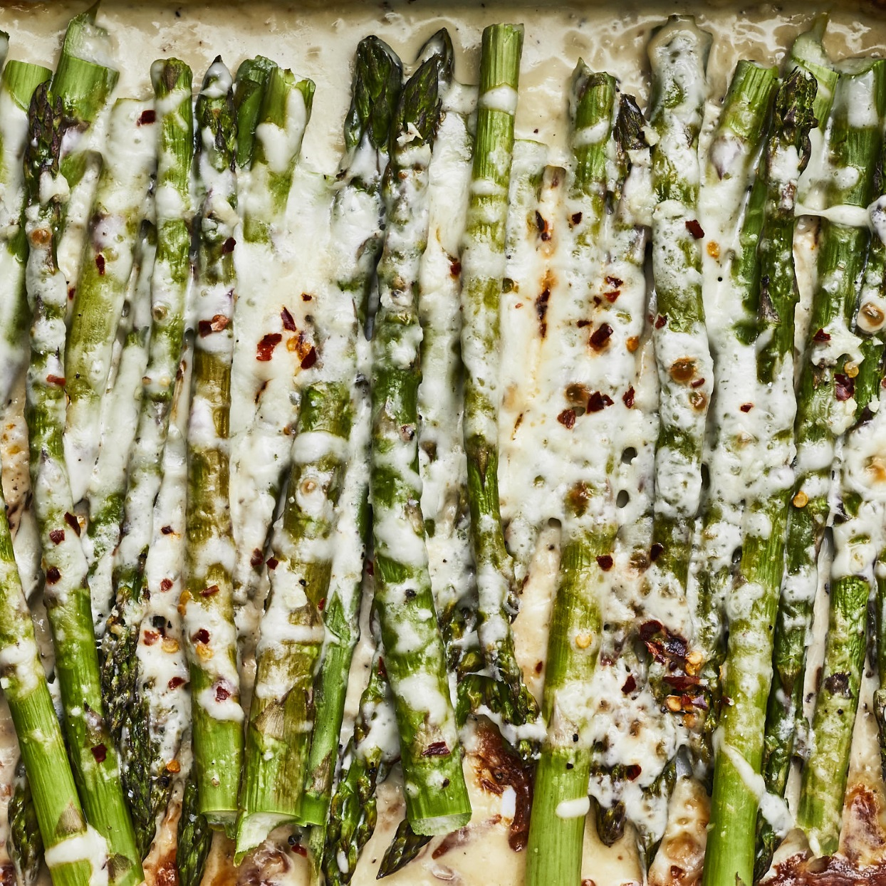 In this cheesy baked asparagus recipe, asparagus spears are roasted whole smothered in a creamy, cheesy garlic sauce. This low-carb side dish is a great way to entice picky eaters to eat their veggies! Pair it with roast chicken or steak. Source: EatingWell.com, January 2020
