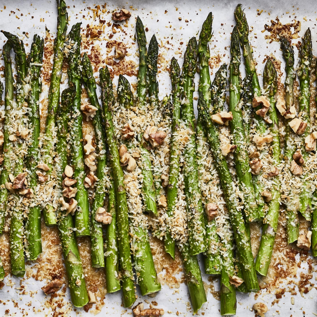 In this garlic-Parmesan-crusted asparagus recipe, we combine Parmesan cheese, whole-wheat panko breadcrumbs and walnuts for a crispy topping that's baked over asparagus. Roasting the asparagus spears in a hot oven keeps them tender-crisp in this quick side dish! Source: EatingWell.com, January 2020