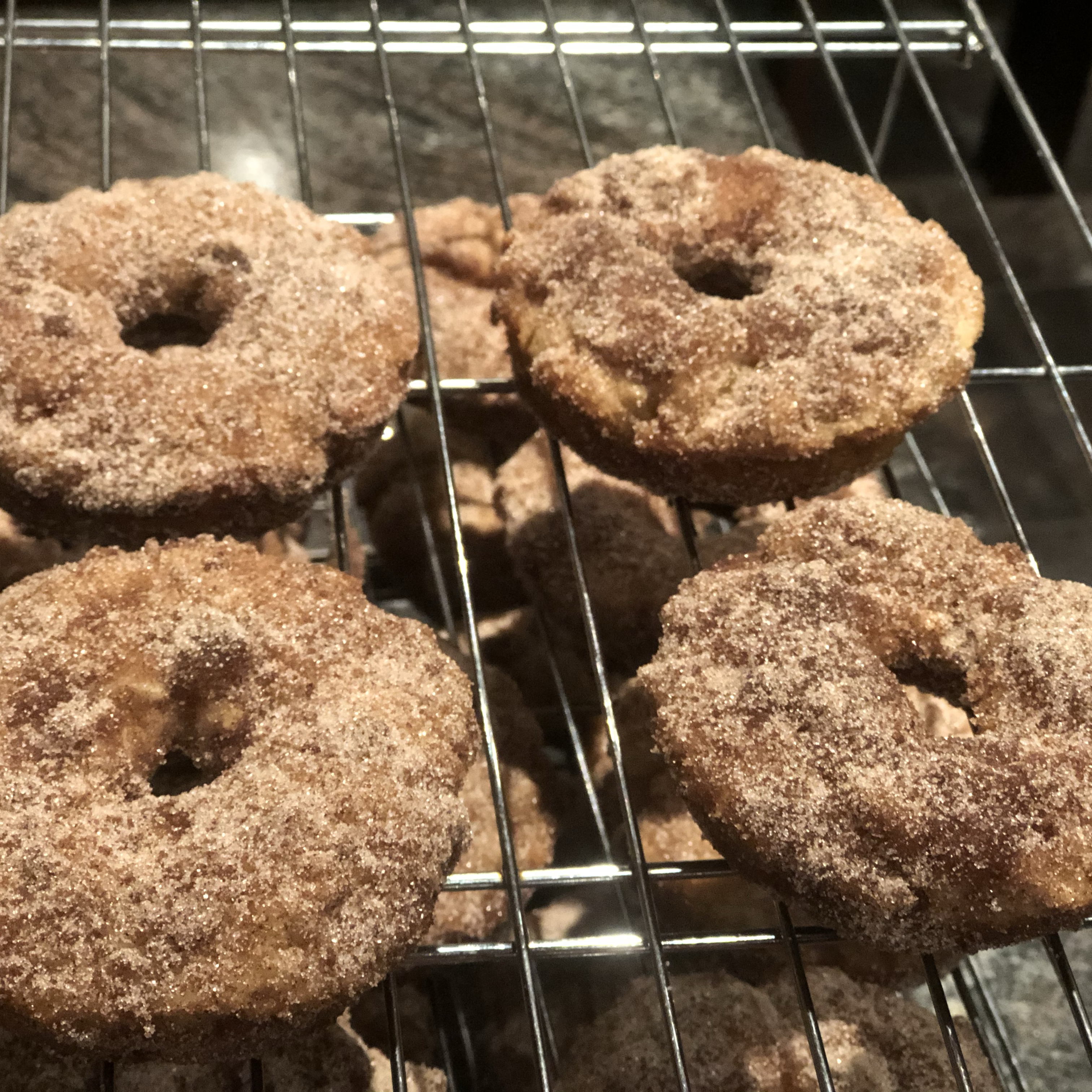 """These easy and delicious baked apple doughnuts are tender, sweet, and studded with pieces of tart apple,"" says summer. ""The trick is to coat the dough in lots of cinnamon sugar, and then bake them so they are still soft on the inside and have a wonderful sugar crust on the outside. Enjoy with coffee and a crossword!"""