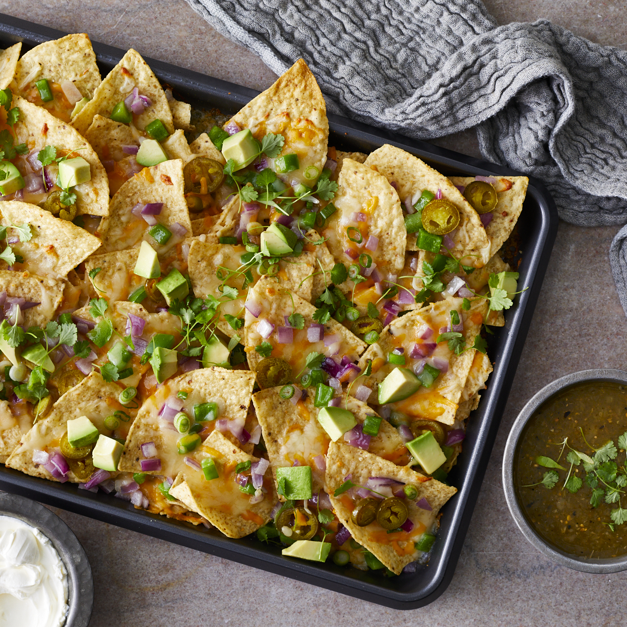 "This quick and easy Super Bowl recipe has been referred to as ""the best nachos people have ever had."" With easy-to-find ingredients, an optional pop of tang and spice from the pickled jalapeños, and the salsa verde and sour cream for serving, we think it's earned its title! Source: EatingWell.com, January 2020"