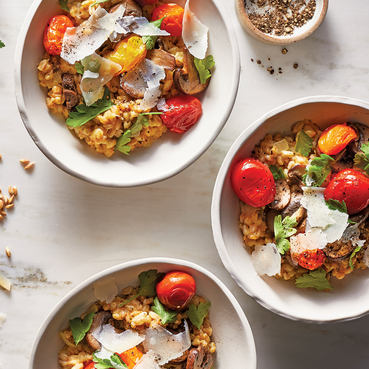 "Instead of arborio rice, this creamy grain dish features the bold nuttiness of farro, which pairs nicely with the black pepper and Parmesan. The cherry tomatoes add a nice touch of juicy sweetness, and the cremini mushrooms give a ""meaty"" feel to this vegetarian main dish. Source: 400 Calorie Recipes"