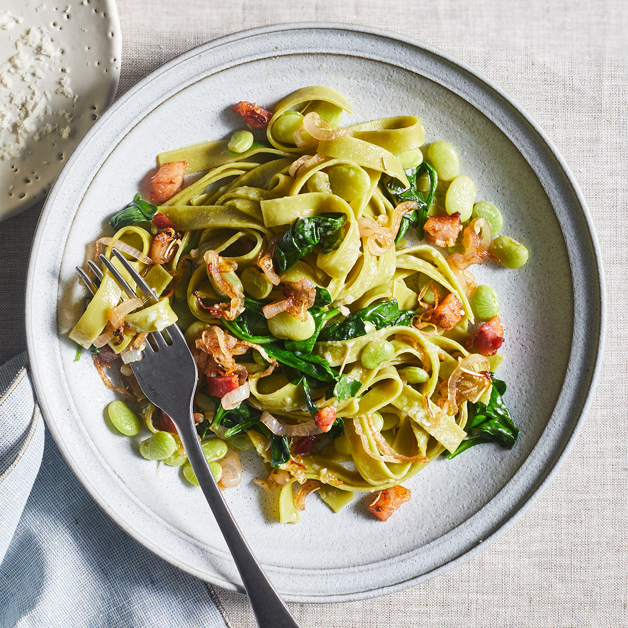 We opt for fresh spinach pasta here--it cooks quickly and adds a pop of color. Cooking lima beans in pancetta drippings infuses them with flavor.