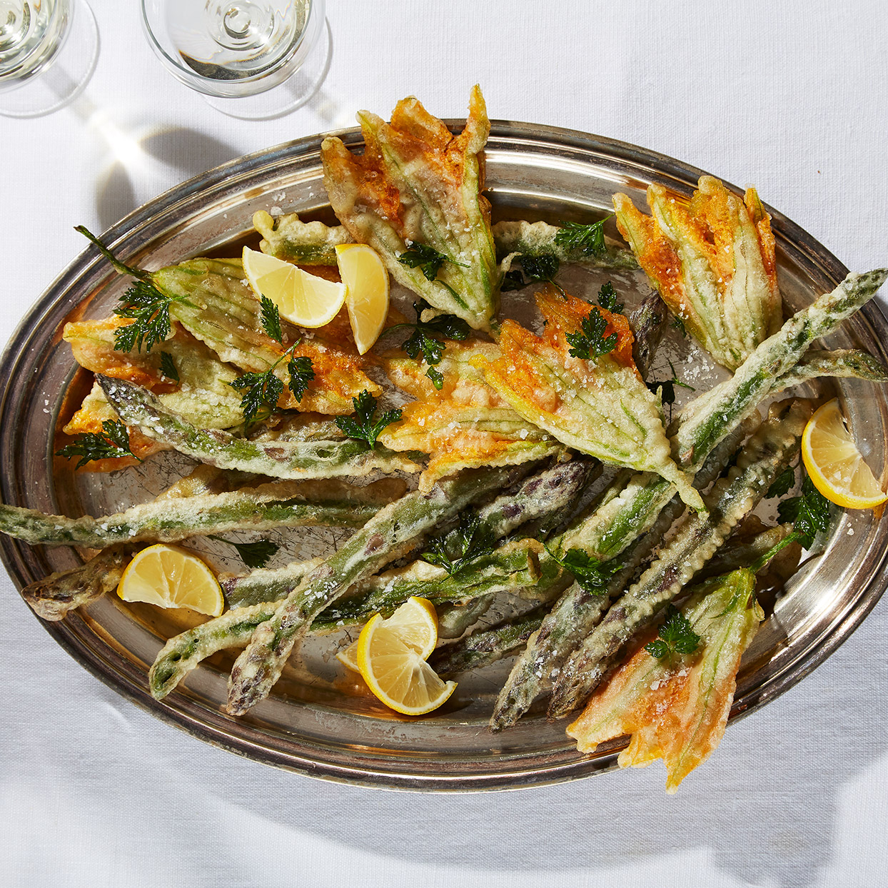 Fritto misto, mixed fried foods, is a typical Italian nibble. Be sure to salt the asparagus and blossoms as soon as they're out of the oil so that the crystals will stick to the food. Source: EatingWell Magazine, March 2020