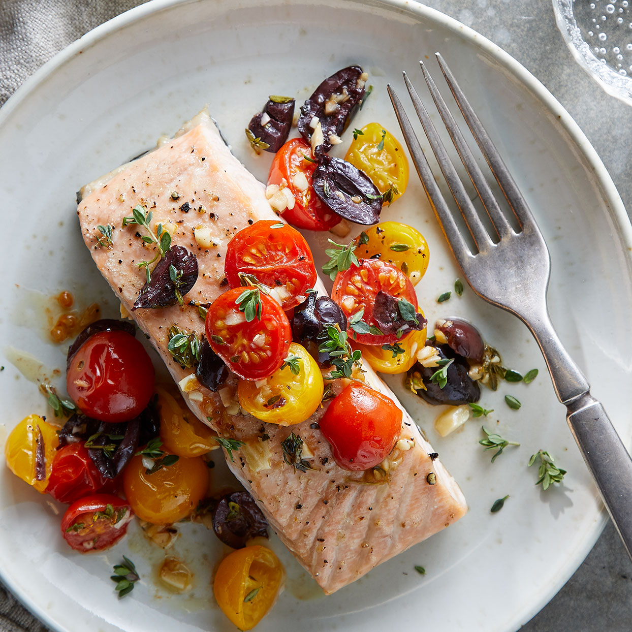 Keep the mess to minimum with this easy sheet-pan dinner. Cherry tomato halves roast alongside salmon fillets and make a delicious topping combined with olives, garlic and thyme in this easy fuss-free dinner.