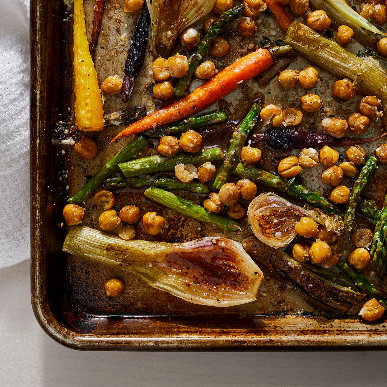 A tangy, balsamic dressing and nutty Parmesan cheese combine to coat tender roasted vegetables and chickpeas in this springy vegetarian dinner. To keep it vegetarian, serve it over quinoa or, for meat-eaters, serve with roasted chicken or pan-seared fish.