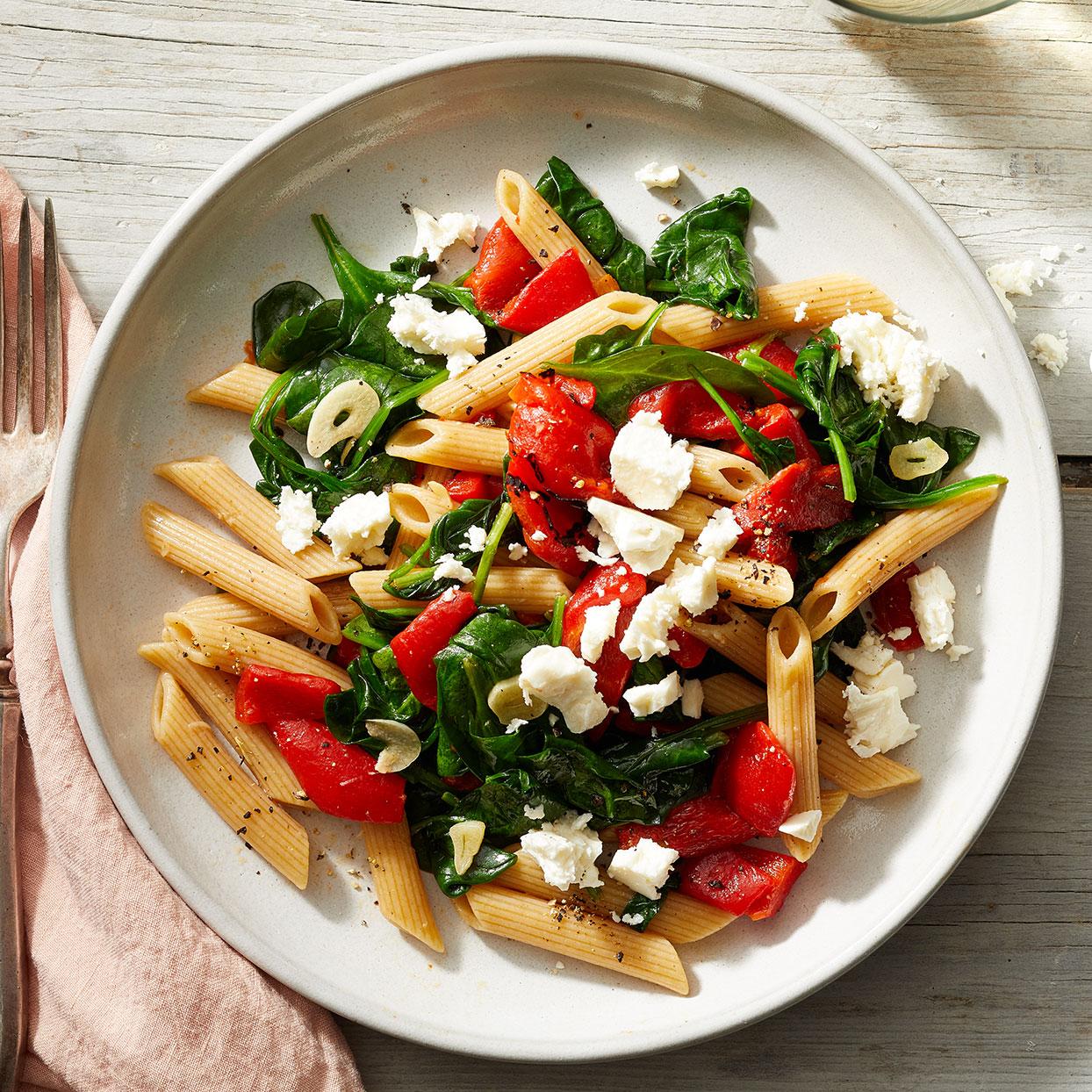 "In this quick 20-minute dinner recipe, tender penne pasta is combined with garlic, roasted red peppers and spinach and topped with crumbled feta cheese for a fast and easy Mediterranean-inspired meal. This recipe was graciously shared by EatingWell reader Dottie Carpenter, who states, ""Recipes are no good if they're not shared!"" Source: EatingWell.com, March 2020"