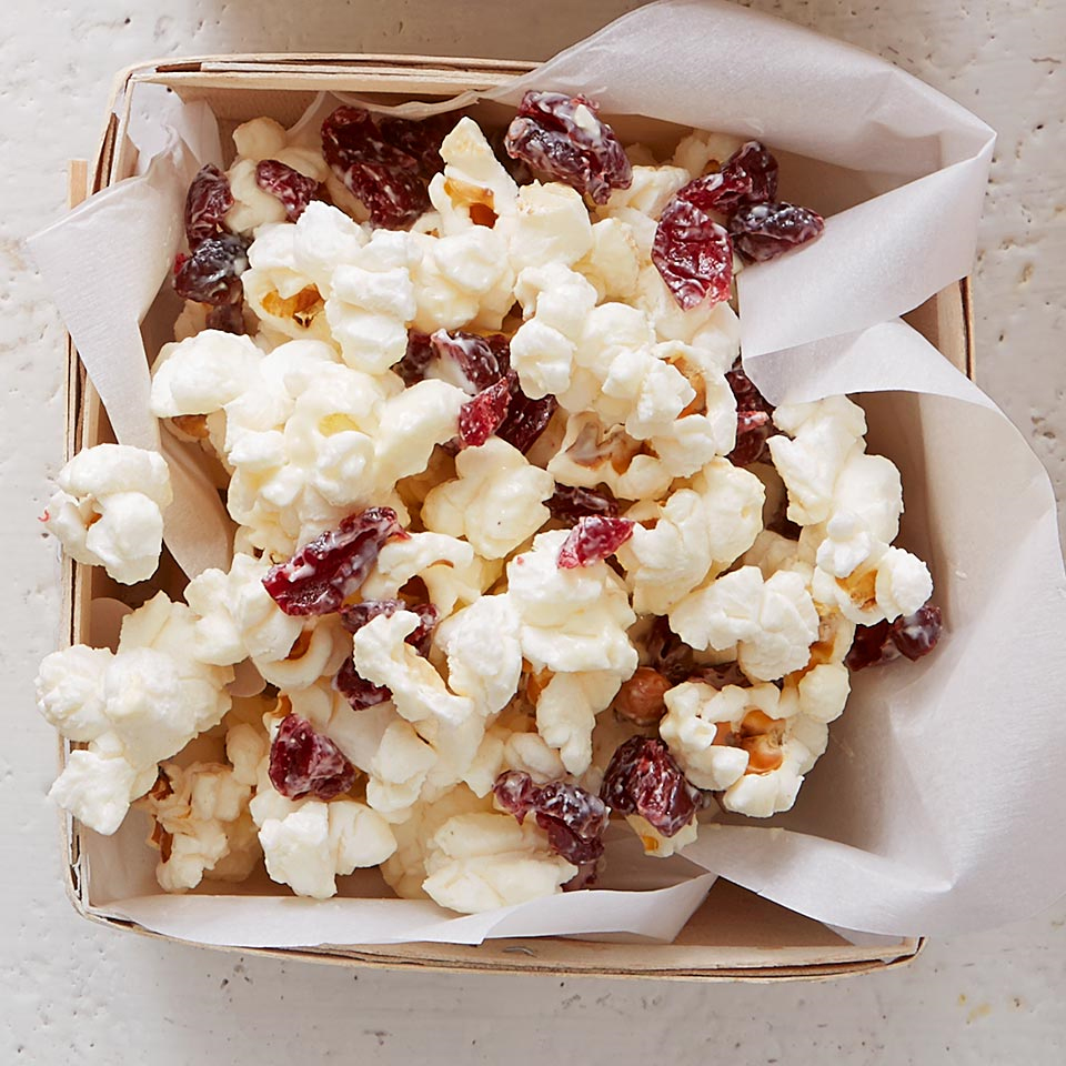 Popcorn and chopped sweetened dried cranberries are tossed together and drizzled with white chocolate.