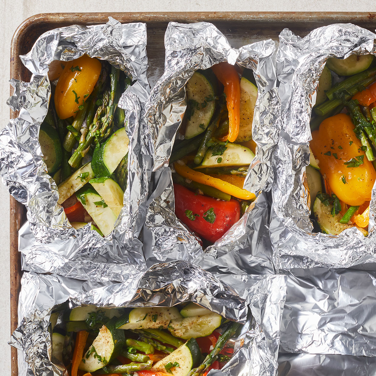 Grilled vegetables in foil is a great recipe to have on hand when camping or cooking over an open fire, but it's also nice on your backyard gas grill too. Here, we cook asparagus, mini peppers and zucchini together with a hint of garlic and butter. Delicious! Source: EatingWell.com, April 2020