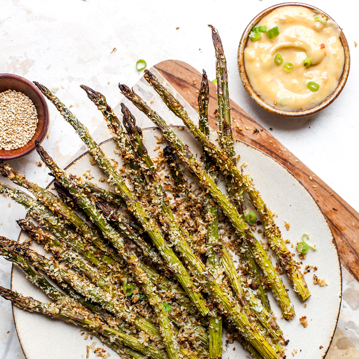 Warm from the oven, these crunchy asparagus spears make a tasty side dish or cocktail nibble. Before being coated in panko breadcrumbs they are rolled in a flavorful sesame-miso sauce that doubles as a simple dipping sauce.