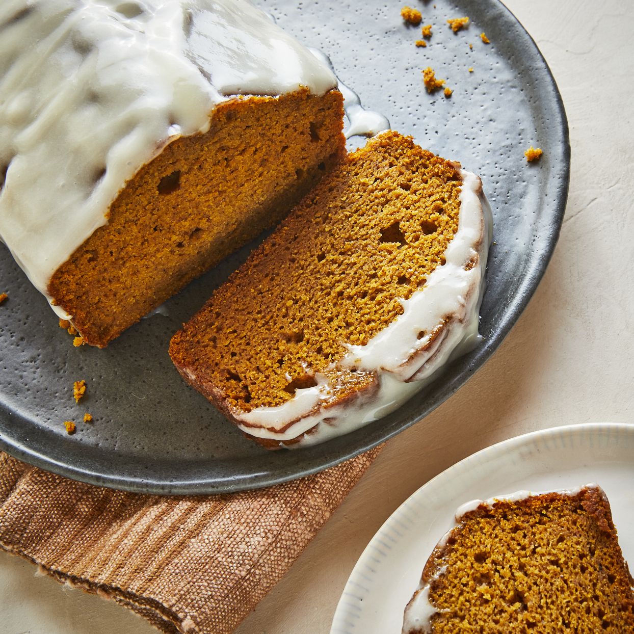 This pumpkin spice bread recipe is a snap to pull together. Pumpkin puree and maple syrup add sweetness to help cut down the amount of added sugar while ensuring this healthy loaf stays moist and tender. This easy quick bread is finished off with a sweetened cream cheese spread over the top to complement the spices.