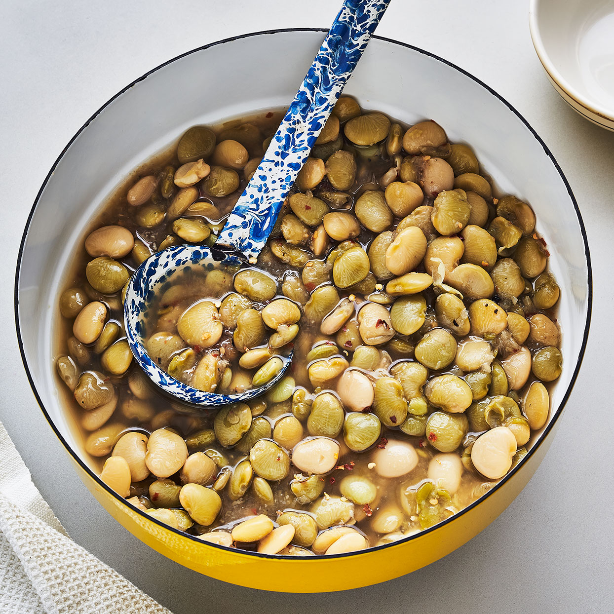 This lima bean recipe is the creation of Mable Clarke, a South Carolina cook and activist. This side dish is on the menu for Clarke's monthly fish fry that she started to save the Soapstone Baptist Church. No need for ham hocks with this recipe--her onion-rich roast turkey stock gives these humble beans a rich, savory flavor, but store-bought will also do the trick. A long, slow simmer coaxes the creaminess out of the limas.