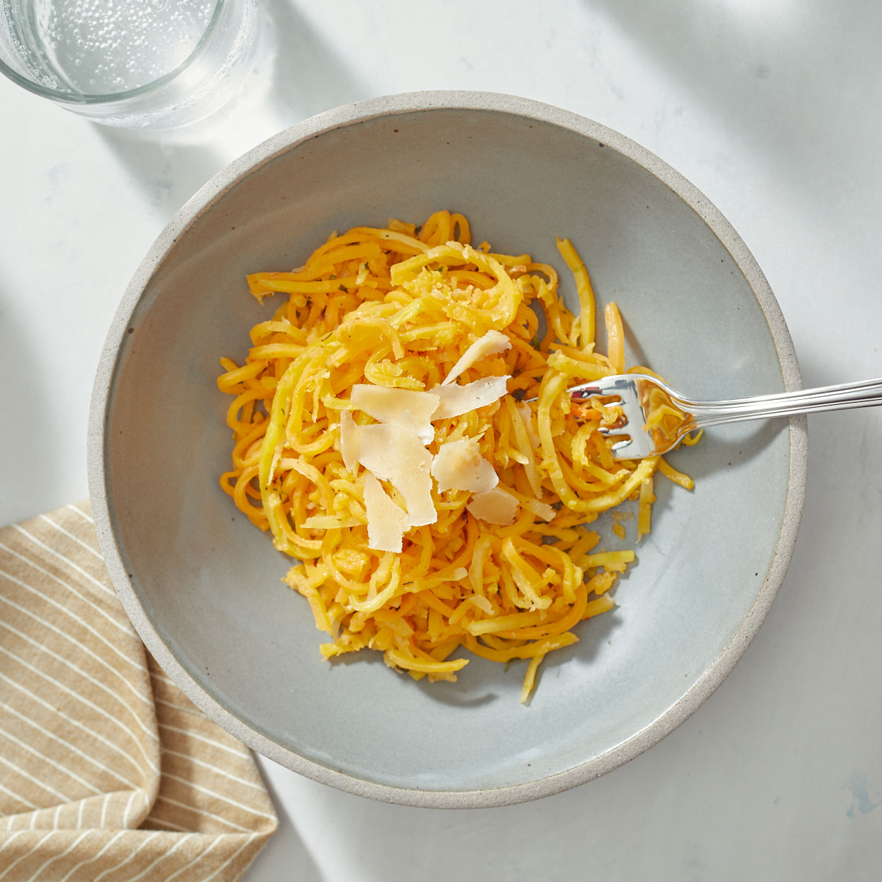 Butternut squash noodles make a great low-carb stand-in for pasta or can be an easy side dish that complements just about everything. We kept this recipe simple with just a hint of fresh thyme and savory Parmesan cheese. Look for fresh or frozen butternut squash noodles or spiralize them yourself using the long, thin neck of a large squash.