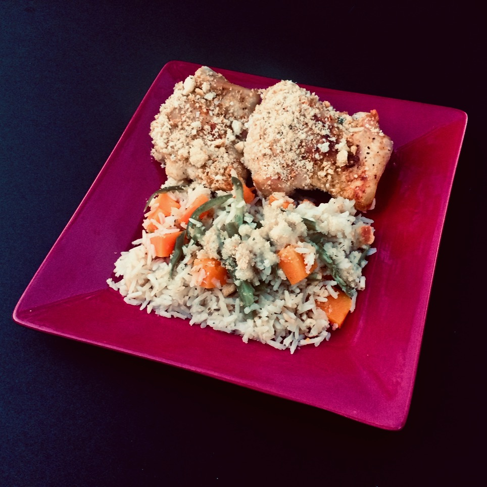 A delicious meal featuring chicken thighs, rice, butternut squash, green beans, and a crunchy finish thanks to crushed croutons.